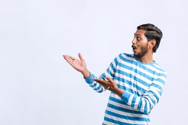 Jovem indiano com uma expressão chocante e mostrando a direção com a mão