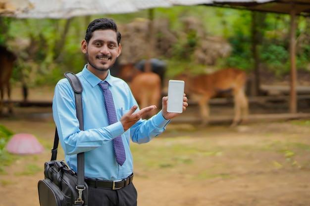 Jovem indiano de banco ou agrônomo mostrando smartphone na casa de fazendeiros