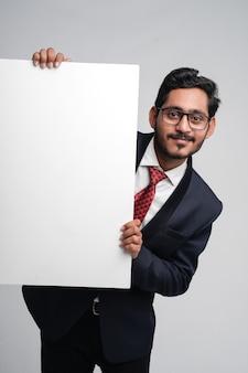 Jovem indiano de negócios segurando uma placa em branco