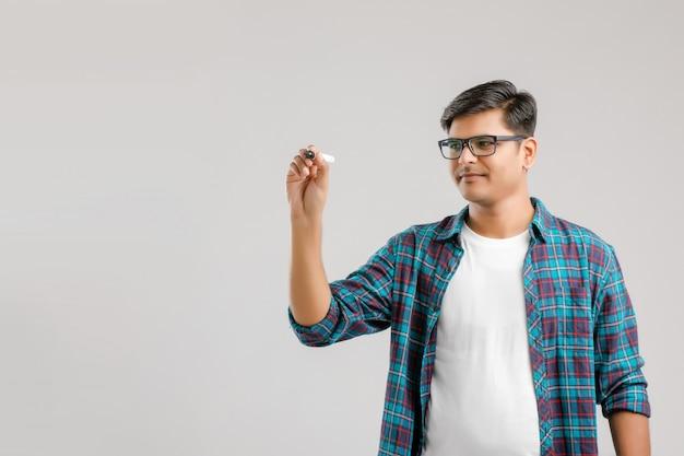 Jovem indiano de óculos e escrevendo algo sobre uma placa de gravação de vidro
