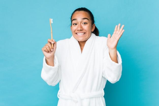 Jovem indiano de raça mista, segurando uma escova de dentes, comemorando uma vitória ou sucesso