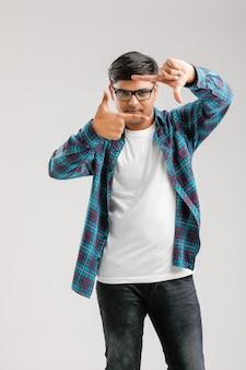 Jovem indiano fazendo moldura com a mão sobre o branco
