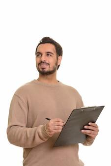 Jovem indiano feliz escrevendo um relatório na prancheta enquanto pensa