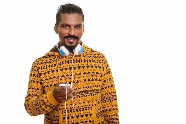 Jovem indiano feliz sorrindo, segurando um telefone celular e usando fones de ouvido no pescoço isolado