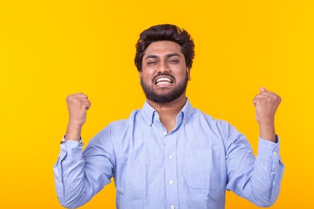 Jovem indiano homem moreno regozija-se posando em uma parede amarela. conceito de sucesso e vitória.