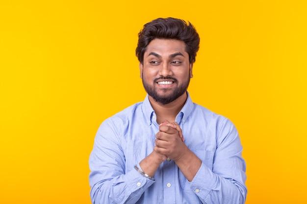 Jovem indiano indiano, morena, exultante, posando em uma parede amarela