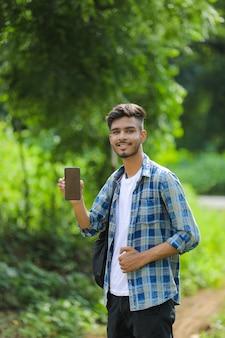 Jovem indiano mostrando a tela do celular