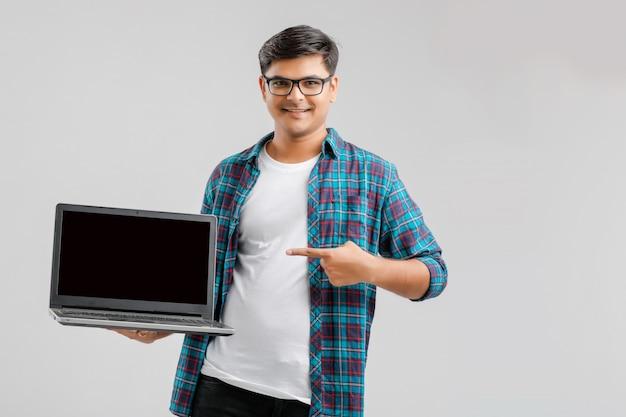 Jovem indiano mostrando a tela do laptop