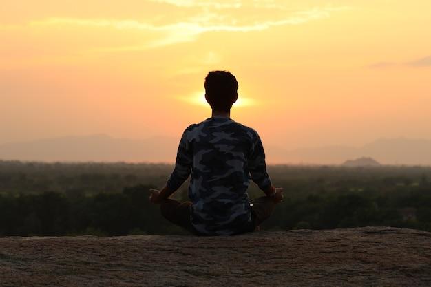 Jovem indiano no topo da montanha sentado em pose de ioga.