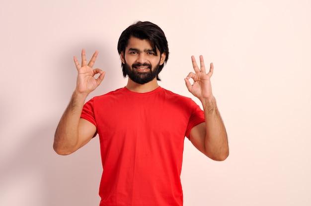 Jovem indiano olhando para a câmera e mostrando sinal de ok com as duas mãos gesticulando e sorrindo