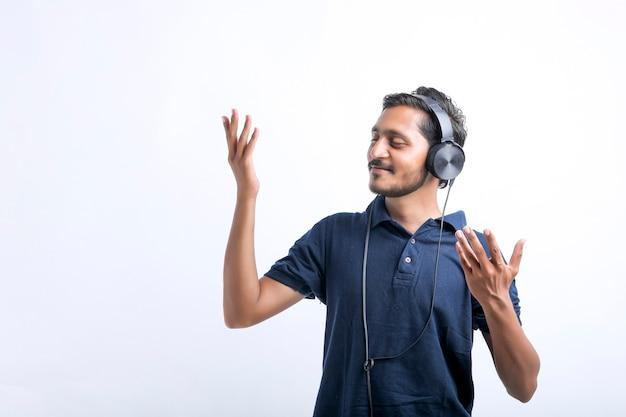 Jovem indiano ouvindo música e mostrando expressão sobre fundo branco.