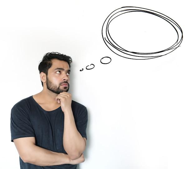 Jovem indiano pensando em um balão de pensamento em fundo branco