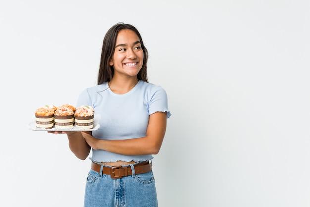 Jovem indiano segurando um doce bolos sorrindo confiante com braços cruzados
