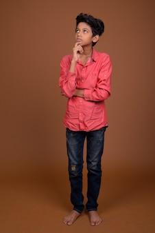Jovem indiano usando roupas casuais elegantes em um fundo marrom