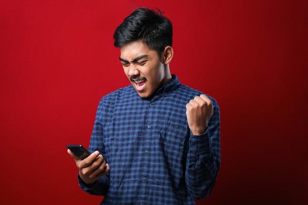Jovem indiano usando smartphone em pé sobre um fundo vermelho isolado, gritando com orgulho e comemorando a vitória e o sucesso, muito animado e exaltando a emoção