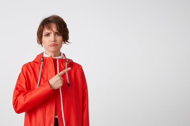 Jovem infeliz fofa de cabelos curtos vestida com capa de chuva vermelha, olhando com expressão triste, quer chamar sua atenção para o espaço da cópia, aponta o dedo para a direita. em pé.