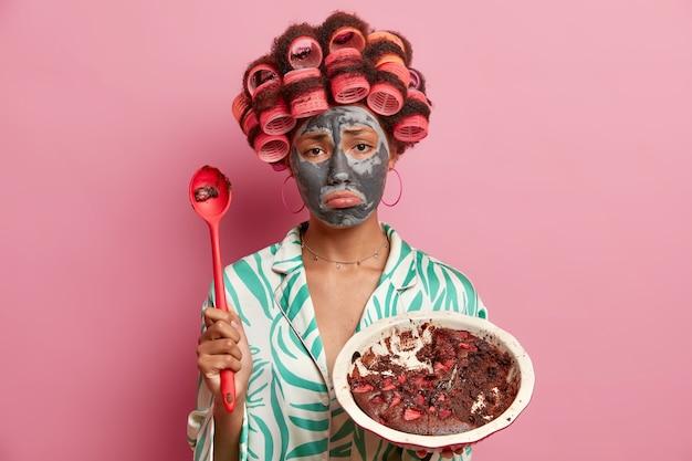 Jovem infeliz frustrada franze os lábios parece tristemente aplica máscara nutritiva de argila para cuidar da pele faz corte de cabelo encaracolado come bolo de chocolate com colher grande vestida com roupas domésticas