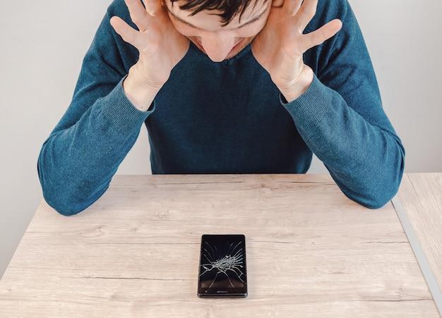 Jovem infeliz olhando para seu smartphone com uma tela quebrada