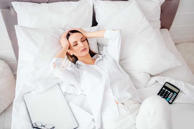 Jovem infeliz recebeu aviso de dívida bancária ou despejo, sentindo-se mal deitada na cama, más notícias, dor de cabeça