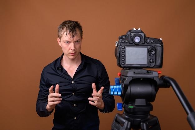 Jovem influenciador fazendo vlogs com câmera dslr