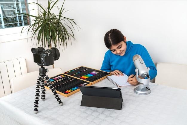 Jovem influenciadora e blogueira transmitindo ao vivo uma aula de pintura com giz de cera de sua sala de estar com uma câmera, tablet e microfone em uma plataforma de vídeo ou rede social