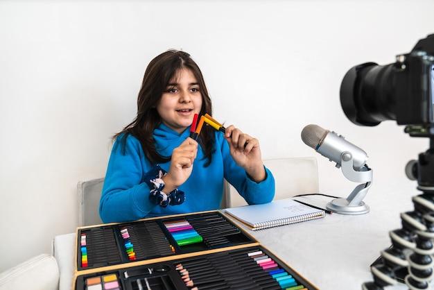 Jovem influenciadora e blogueira transmitindo ao vivo uma aula de pintura com giz de cera em sua sala de estar, rindo, olhando para a câmera e falando ao microfone em um vídeo ou plataforma de mídia social
