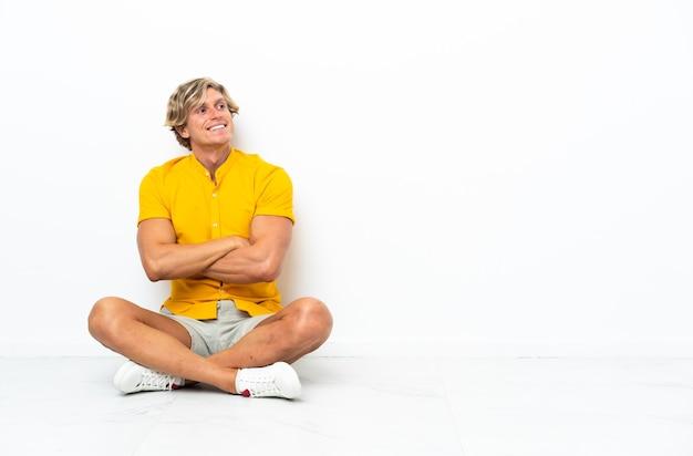 Jovem inglês sentado no chão com os braços cruzados e feliz