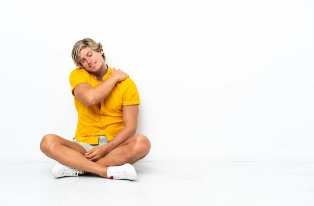 Jovem inglês sentado no chão sofrendo de dores no ombro por ter feito um esforço