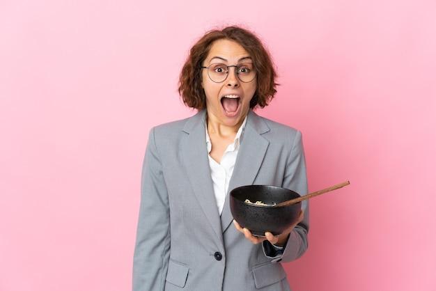 Jovem inglesa em rosa com expressão facial de surpresa e choque, segurando uma tigela de macarrão com pauzinhos