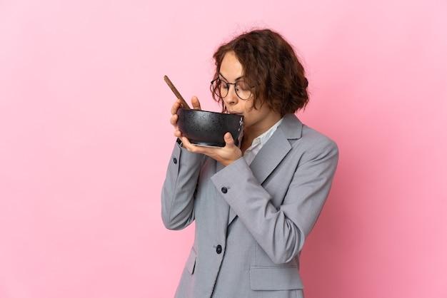 Jovem inglesa em rosa segurando uma tigela de macarrão com pauzinhos e comendo