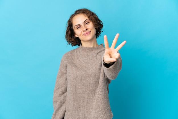 Jovem inglesa feliz em azul e contando três com os dedos