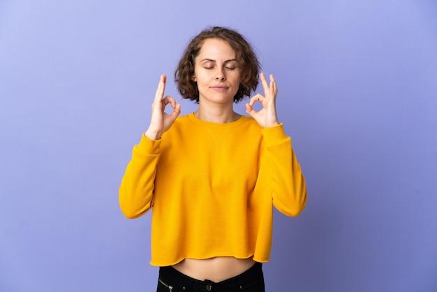 Jovem inglesa isolada em um fundo roxo em pose zen