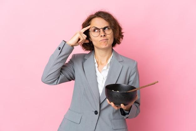 Jovem inglesa isolada em uma parede rosa com dúvidas e com uma expressão facial confusa enquanto segura uma tigela de macarrão com pauzinhos