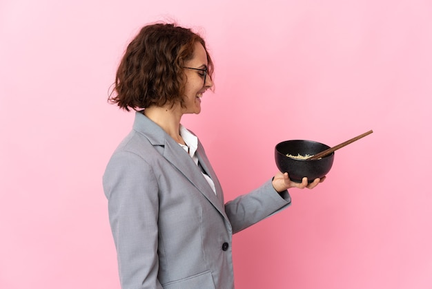 Jovem inglesa isolada em uma parede rosa com uma expressão feliz, segurando uma tigela de macarrão com pauzinhos