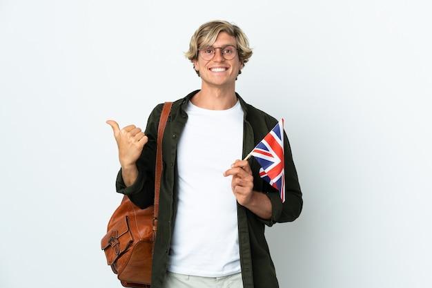 Jovem inglesa segurando uma bandeira do reino unido apontando para o lado para apresentar um produto