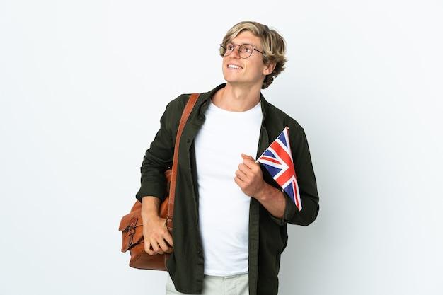 Jovem inglesa segurando uma bandeira do reino unido, pensando uma ideia enquanto olha para cima