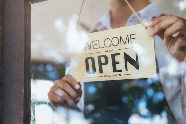 Jovem inicialização café café owener aberto e bem-vindo cliente.