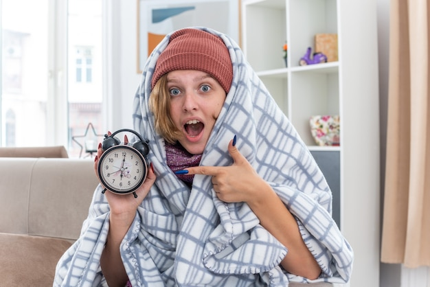 Jovem insalubre com um chapéu enrolada em um cobertor, segurando um despertador surpresa, sentada no sofá em uma sala iluminada