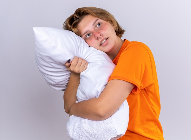 Jovem insalubre em uma camiseta laranja segurando um travesseiro olhando de lado pensando positivo em pé