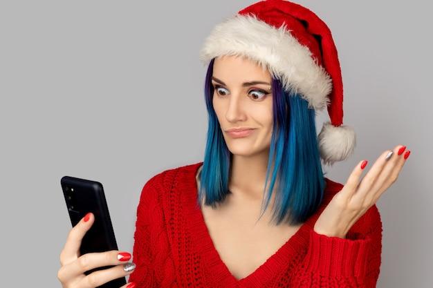 Jovem insatisfeita com chapéu de papai noel com smartphone sobre fundo cinza. conceito de venda de compras de natal