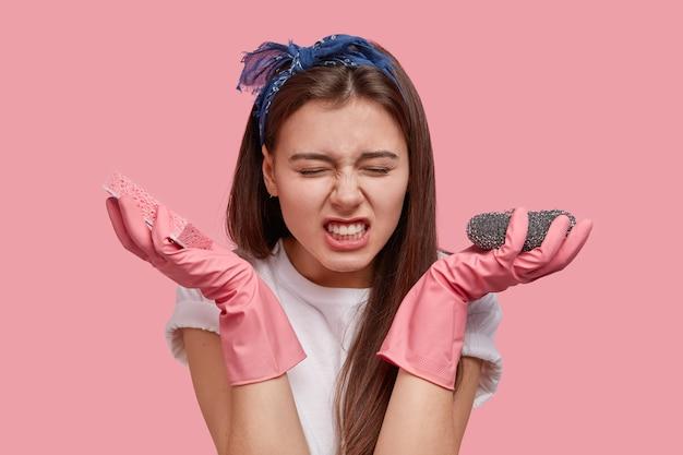 Jovem insatisfeita de cabelos escuros trinca os dentes, usa bandana, luvas de borracha, segura o esfregão, zangada com o trabalho doméstico