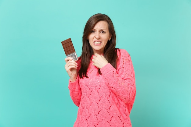 Jovem insatisfeita preocupada em uma camisola de malha rosa, segurando na mão a barra de chocolate isolada no fundo da parede azul turquesa, retrato de estúdio. conceito de estilo de vida de pessoas. simule o espaço da cópia.