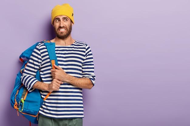 Jovem insatisfeito com a barba por fazer, sente-se cansado após uma longa caminhada a pé, usa capacete amarelo e suéter de marinheiro, cerra os dentes, parece desagradável, posa contra parede roxa, espaço em branco à direita