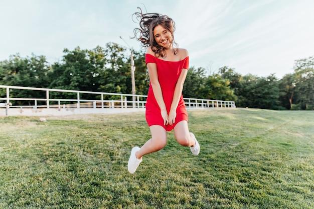 Jovem inspirada pulando no parque e sorrindo. linda menina morena com vestido vermelho, se divertindo no fim de semana de verão.