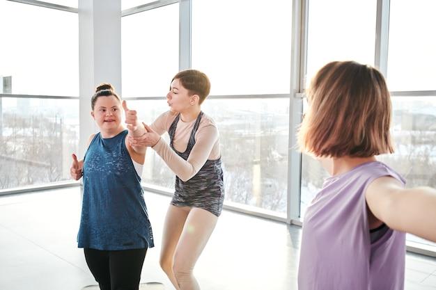 Jovem instrutor de ioga e condicionamento físico em roupas esportivas em pé ao lado da garota deficiente e ajudando-a com um dos exercícios durante o treinamento físico na academia