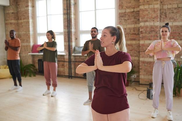 Jovem instrutor mostrando os exercícios para o grupo durante aula de ioga na academia