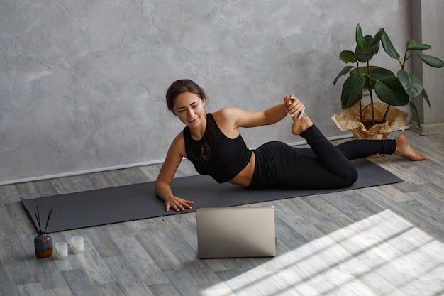 Jovem instrutora de ioga esportiva treinando online, fazendo um vídeo de aulas de ioga na câmera do laptop