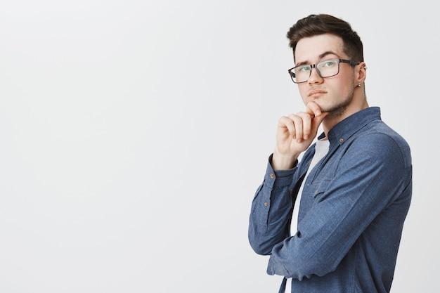 Jovem inteligente de óculos parecendo pensativo, ponderando sobre uma ideia