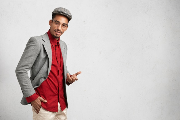 Jovem inteligente usa boné, camisa formal vermelha com paletó e óculos redondos, tem expressão confiante