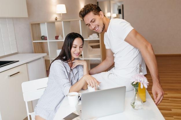 Jovem interessada apontando para a tela do laptop com um sorriso, passando um tempo com o namorado pela manhã
